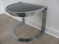 A nest of 3 chrome & glass, semicircular tables