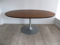 A rosewood 'tulip' table on an aluminium base. Arkana