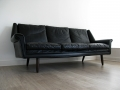 A Danish black leather sofa on solid teak legs