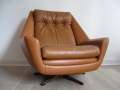 A large tan leather Danish swivel chair